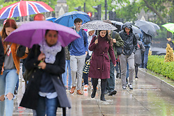 © Licensed to London News Pictures. 10/06/2019. London, UK. Tourists shelter from the rain beneath umbrellas and walk though puddle of water as rain falls in the capital. The Met Office has issued an amber warning for more rain, covering London and parts of southeast England later today.  Photo credit: Dinendra Haria/LNP