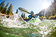 Underwater view of a young woman kayaker splashing and enjoying a sunny day kayaking on the Snake River of Wyoming