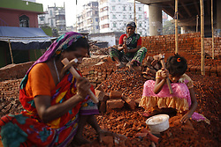 November 3, 2018 - Dhaka, Bangladesh - Female day labourer with a child breaks bricks at a brick factory in Keraniganj. Female day laboures earn around 20 US dollars per week over eight hours each day as they come from country side in a hope for better life. (Credit Image: © MD Mehedi Hasan/ZUMA Wire)