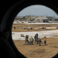 North of the Arctic Circle in Russia, nomadic Komi Reindeer herders, who are visiting Snopa village to resupply their provisions, watch as a helicopter ferries people back to the nearest big city, Arkhangel'sk. (as viewed from the helicopter)