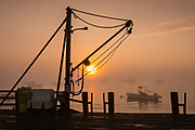 A winch on the wharf as lobstermen prepare to head out on the water during a foggy morning sunrise at Five Islands Harbor, Maine.