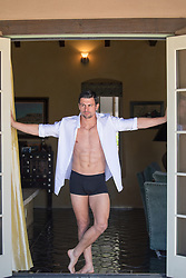 hot man in underwear and an open button down shirt in a doorway at home