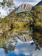 The Du Cane Range reflects in a pond on the Overland Track, in Cradle Mountain-Lake St Clair National Park, Tasmania, Australia. The most extensive dolerite formations in the world dominate the landscape of Tasmania, where magma intruded into a thin veneer of Permian and Triassic rocks over perhaps a million years during the Jurassic breakup of supercontinent Gondwana in the Southern Hemisphere, forming vast dolerite/diabase sills and dike swarms. (North American geologists use the term diabase instead of dolerite to refer to the fresh, unaltered rock.) The Tasmanian Wilderness was honored as a UNESCO World Heritage Site in 1982, expanded in 1989.