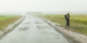 Woman with hat walking on side of road in rain storm from Cyclone Giri, Mrauk U