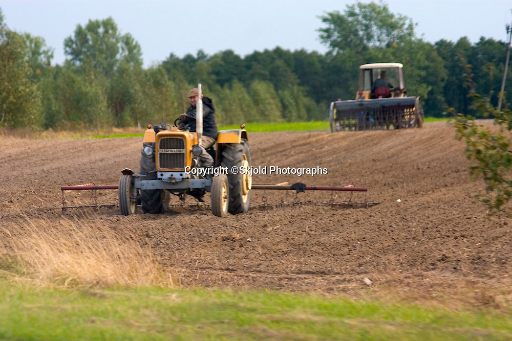 Farmers using tractors to cultivate fields in the Polish countryside. Zawady Central Poland