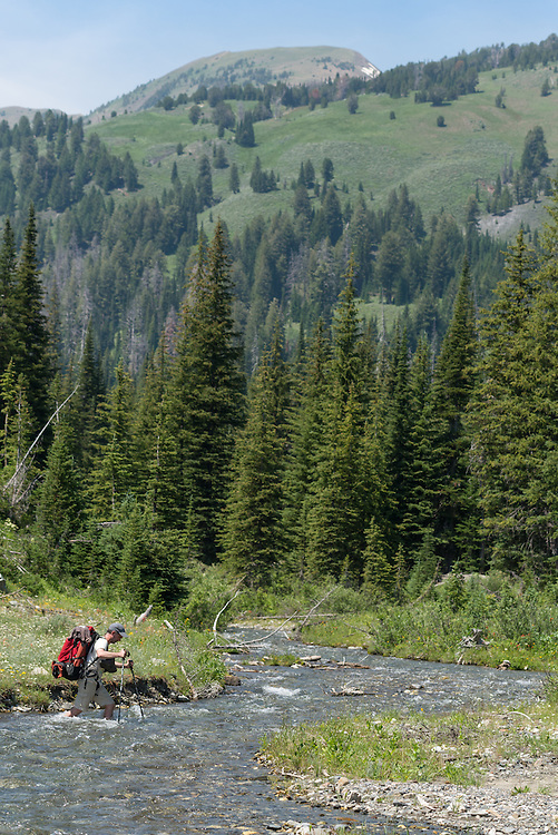 Backpacker fording a stream in Oregon's Wallowa Mountains.