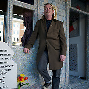Ireland: Irish artist Frank Buckley stands beside the main entrance of his Billion Euro House art installation in central Dublin. ..Worthless euros, taken out of circulation and shredded by Irelands Central Bank, formes the interior walls of an apartment that Mr. Buckley does not own in a building left vacant by the countrys economic ruin...The artist decided to call the apartment  built from thousands of bricks of shredded, decommissioned cash (each brick contains, roughly, what used to be 50,000 euros)  the Billion Euro House. He reckons that about 1.4 billion euros actually went into it, but the joke, of course, is that it is worth simultaneously so much and so little...A large gravestone beside the main door, announces that Irish sovereignty died in 2010, the year that the government accepted an international bailout so larded with onerous conditions that the Irish will be paying for it for years to come. (Paulo Nunes dos Santos/Polaris)
