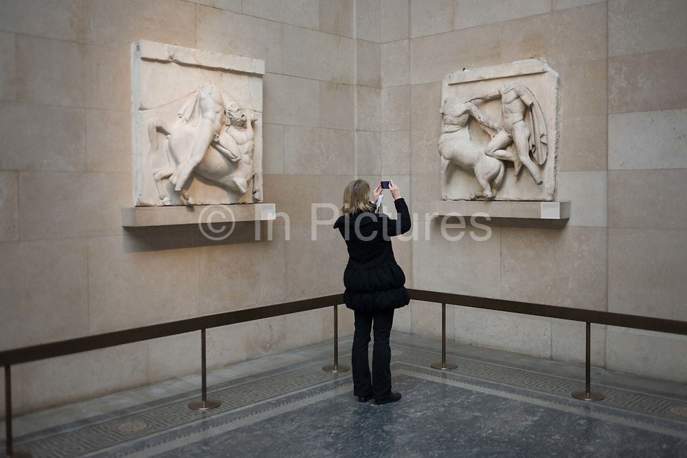 Woman photographs photograps the Ancient Greek Parthenon Metopes also knows as the Elgin Marbles in the British Museum. 92 Metopes were rectangular slabs placed over the columns of the Athens Parthenon temple depicting scenes from Greek mythology. The Elgin Marbles are a collection of classical Greek marble sculptures (mostly by Phidias and his pupils), inscriptions and architectural members that originally were part of the Parthenon and other buildings on the Acropolis of Athens. Thomas Bruce, 7th Earl of Elgin, the British ambassador to the Ottoman Empire from 1799–1803, obtained a controversial permit from the Ottoman authorities to remove pieces from the Acropolis. From 1801 to 1812 Elgin's agents removed about half of the surviving sculptures of the Parthenon