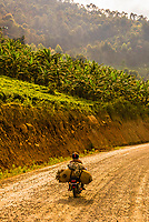 Man on motorcycle on a dirt road between Queen Elizabeth NP and Bwindi Impenetrable Forest, Uganda.