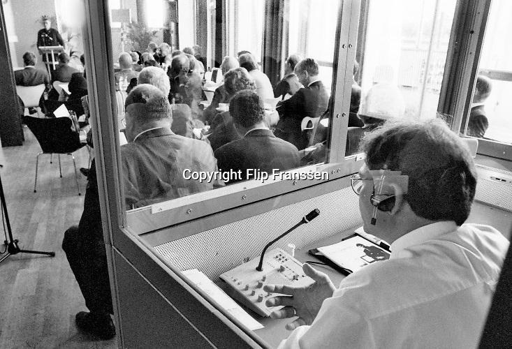 Nederland, Rotterdam, 5-6- 1995 Congres in Hotel New York op de wilhelminakade. Een vertaler, tolk, doet zijn werk in een klein hokje .Foto: Flip Franssen