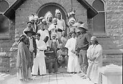 9336-MA32. Indian group on the steps of Holy Family Catholic Church, Burns, Oregon. Identifications: extreme left Takama (mother of Gladys Macey), man 2nd from left with hat glancing left- Clyde Johnson, man 3rd from left on step with no hat- husband of Grace White, woman left of Father Huel with white scarf over hair- Grace White, behind her with cap- Teddy Dick, center- Father Huel, seated center on lower step with hat- Chief Captain Louey, old man seated on second step to right- William Johnson, middle aged man behind him- Jim Tooie, alter boy unidentified, partially obscured young man to the right of the right altar boy- Betchel Capp (son of Johnny and Ada Capp), extreme right standing man with hat- Johnny Capp, woman- Ada Capp. Indians with headdresses are from Pendleton.