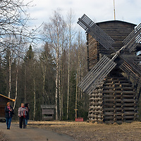 Russian tourists walk past an historic wooden windmill relocated to the Malye Korely outdoor museum, in a taiga forest near the northern port of Arkhangel'sk.