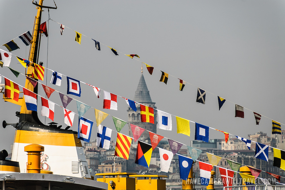 Istanbul's Tower of Galata seen through the flags on top of a ferry from across the Golden Horn.