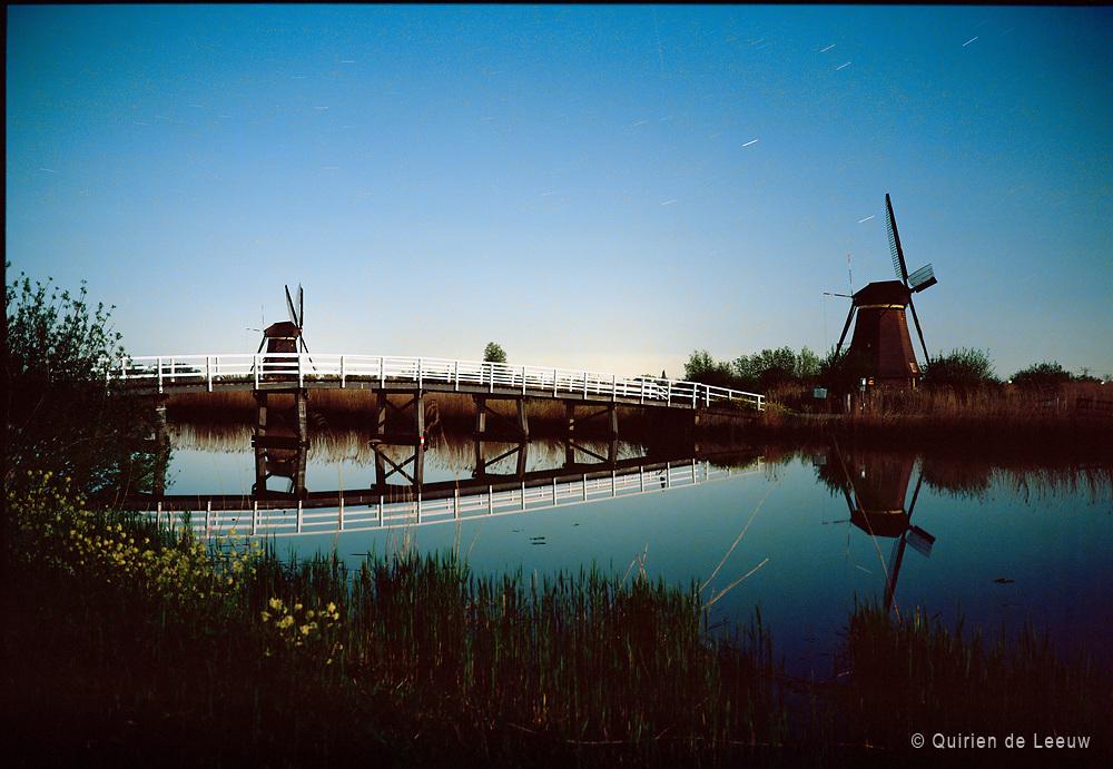 Kinderdijk windmills at full moon night. UNECSCO heritage site.