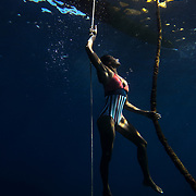 Female swimming up the anchor line to her outrigger canoe in Hawaii.