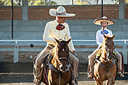 Juan Franco, Jr. and his father Juan Franco, Sr. on horseback at the family Charreria practice session in the Jalisco Highlands town of Capilla de Guadalupe, Mexico. The Franco family has dominated Mexican rodeo for 40-years and has won three national championships, five second places and five third places.
