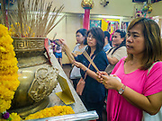 """24 FEBRUARY 2013 - BANGKOK, THAILAND: People pray in the """"coffin temple"""" of the Ruamkatanyu Foundation next to Wat Hua Lamphong. The Ruamkatanyu Foundation provides coffins for Bangkok's indigent and emergency medical services for accident victims in Bangkok. Wat Hua Lamphong is a Royal Buddhist temple, third class, in the Bang Rak District of Bangkok, Thailand. It is located on Rama IV Road, approximately 1km from the city's main Hua Lamphong railway station. An entrance to Sam Yan Station on the Bangkok metro (subway) is located outside the main entrance to the temple compound on Rama IV. Wat Hua Lamphong was renovated in 1996 to mark the 50th anniversary of the ascension to the throne of King Bhumibol Adulyadej (Rama IX) in 1996. The royal seal of what became known as the Kanchanapisek, or Golden Jubilee, year, showing two elephants flanking a multi-tiered umbrella, are featured in the temple's remodeling.     PHOTO BY JACK KURTZ"""
