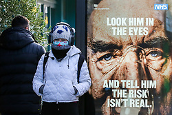 """© Licensed to London News Pictures. 29/01/2021. London, UK. A woman wearing a protective face covering walks past the government's 'Look him in the eyes - And tell him the risk isn't real.' publicity campaign poster in north London. Covid-19 infection rates are continuing to drop across London. But health experts are warning Londoners to follow the lockdown rules, as """"any relaxation would risk a rapid reversal or decline."""" Photo credit: Dinendra Haria/LNP"""