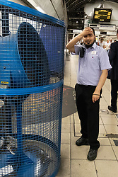 © Licensed to London News Pictures. 26/07/2018. London, UK. A London Underground employee cools off in front of a large fan in Bank tube station during hot weather. Today is predicted to be the hottest day of the year, with temperatures in the capital set to rise up to 35 degrees, as the UK experiences a prolonged heatwave. Photo credit : Tom Nicholson/LNP