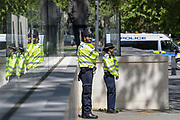Two police officers are reflected in the glassed fence of Scotland Yard, the headquarters of London's Metropolitan Police Service, in London, on Tuesday, May 5, 2020. (Photo/Vudi Xhymshiti)
