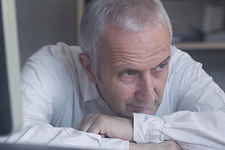 Close-up of a senior businessman sitting in the office and thinking, Freiburg im Breisgau, Baden-Wuerttemberg, Germany