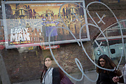 Young women, bus stop graffiti and an ad for the new Aardman Animation's new release Early Man, on 30th January 2018, in the south London borough of Southwark, England.