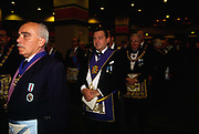 Assembled Freemasons prepare to process into Earls Court, London. Freemasonry, which traces it's modern origins back to the sixteenth century is beased on principles of fraternity and secrecy. Members are sworn to keep silent on their activities and make themselves known to other Freemason's by way of signal (often a handshake).