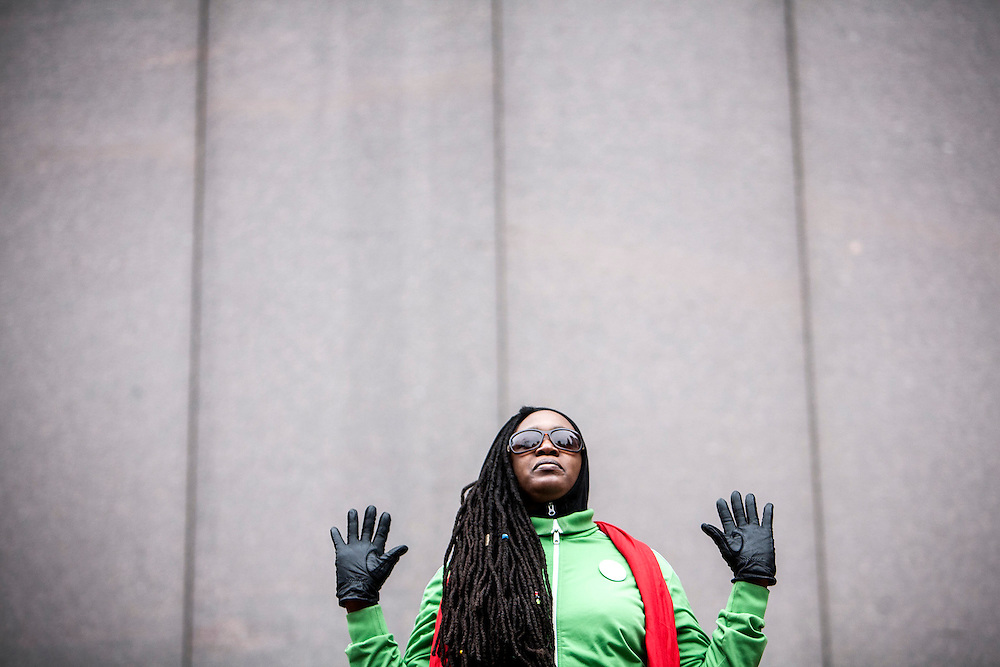 A Black Lives Matter protester stands silent with hands raised at the Million Artist Movement rally at Government Center in Minneapolis December 13, 2014.