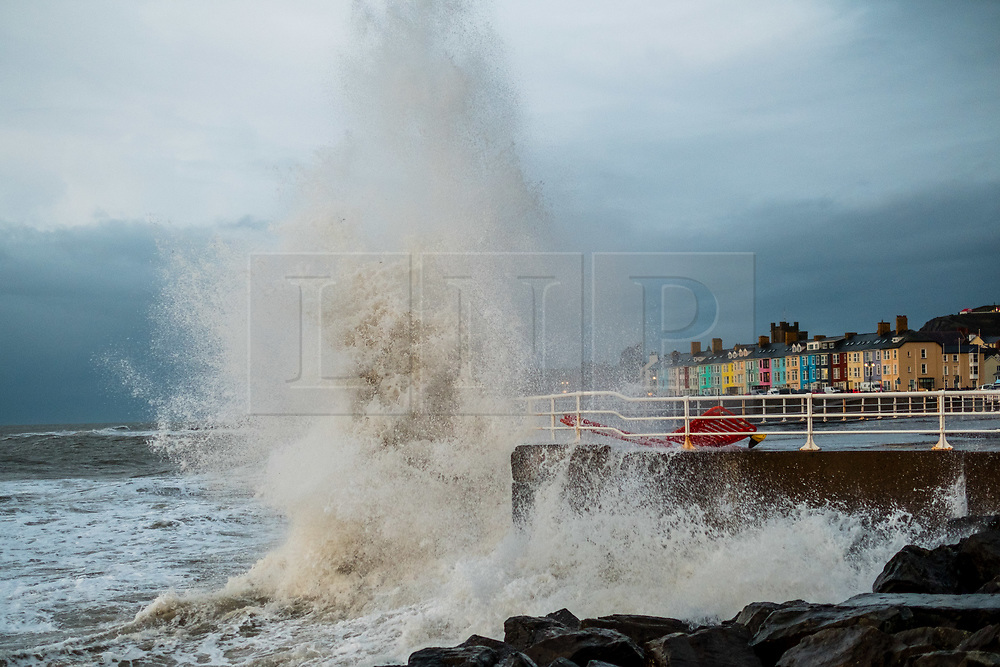 © Licensed to London News Pictures. 19/12/2018. Aberystwyth, UK.  Strong winds and a high tide combine to  hammer huge waves against the sea defences in Aberystwyth on the Cardigan Bay coast of west Wales on a wet and blustery day, with more unsettled weather forecast for the coming days. Photo credit: Keith Morris/LNP