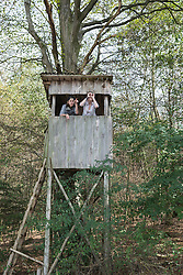 Young female hiker standing on lookout tower and looking into the distance, Bavaria, Germany