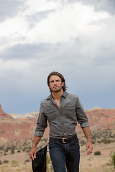 rugged good looking cowboy walking on a ranch in the mountains