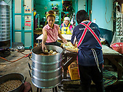 "12 FEBRUARY 2018 - BANGKOK, THAILAND: Women fill steaming racks in a home that makes steamed Chinese buns, called ""bao"" in the Chinatown neighborhood of Bangkok. Bao are eaten at midnight on the Lunar New Year and served to guests during New Year's entertaining. Lunar New Year, also called Tet or Chinese New Year, is 16 February this year. The coming year will be the Year of the Dog. Thailand has a large Chinese community and Lunar New Year is widely celebrated in Thailand, especially in Bangkok and large cities with significant Chinese communities.    PHOTO BY JACK KURTZ"