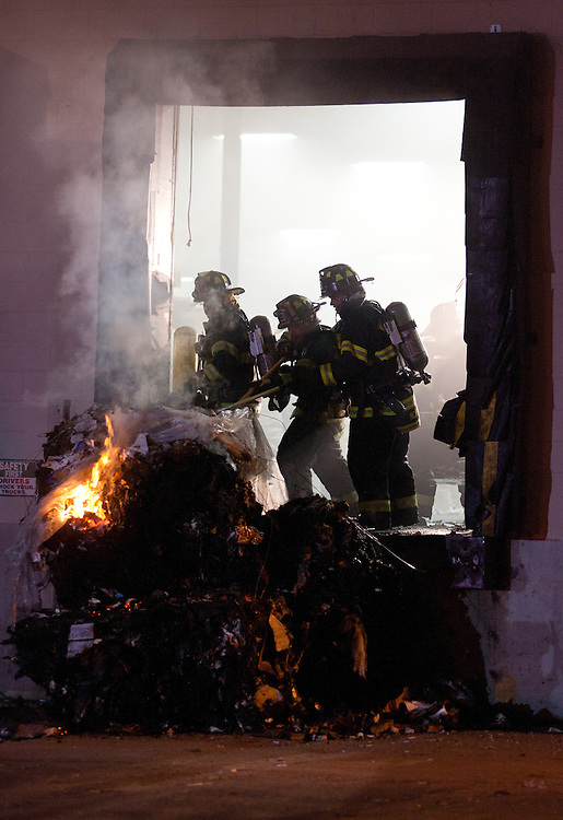 Mansfield, MA 09/13/2011.Firefighters push a burning bale of cardboard out the door of Miller Recycling in Mansfield while fighting a 4 alarm fire there on Tuesday night..Wicked Local Photo by Alex Jones