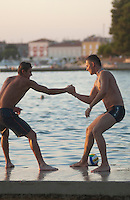Badevergnügen in der Bucht vor Porec. Junge Männer rangeln auf der Kaimauer versuchen sich gegenseitig ins Wasser zu werfen. | Young men playfully establish a rank order on a pier and try to shove each other into the water.