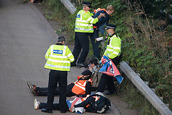 Ockham, UK. 21st September, 2021. Surrey Police officers restrain Insulate Britain climate activists who had block the anticlockwise carriageway of the M25 between Junctions 9 and 10 as part of a campaign intended to push the UK government to make significant legislative change to start lowering emissions. Both carriageways were briefly blocked before being cleared by Surrey Police. The activists are demanding that the government immediately promises both to fully fund and ensure the insulation of all social housing in Britain by 2025 and to produce within four months a legally binding national plan to fully fund and ensure the full low-energy and low-carbon whole-house retrofit, with no externalised costs, of all homes in Britain by 2030.