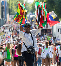 London, August 27 2017. A woman sells flags on Ladbroke Grove as Family Day of the Notting Hill Carnival gets underway. The Notting Hill Carnival is Europe's biggest street party held over two days of the bank holiday weekend, attracting over a million people. © Paul Davey.
