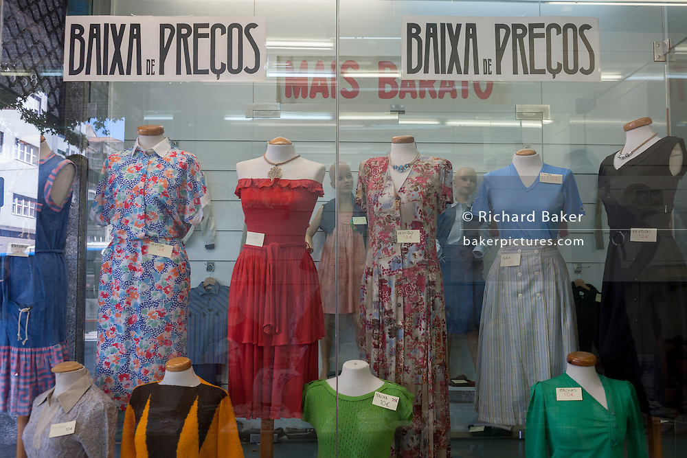 Low prices for second-hand womens' clothes inside a shop window in Porto, Portugal.
