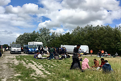 30July2021. Calais, France.<br /> Migrants sit in the grass to eat food as supplied by British founded charity Care4Calais along with other charities offering food, assistance, phone charging, haircuts, clothing, tents and more to migrant refugees in Dunkerque. A new 'Jungle' appears to be springing up from the trees and woods on the outskirts of Dunkerque where conditions are not as hostile or inhospitable as they are currently in Calais 30km to the south.<br /> Photo©; Charlie Varley/varleypix.com