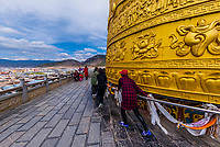 The largest prayer wheel in the world (24 meters tall, 79 feet). The gilt bronze prayer wheel takes a minimum of seven people to turn it.  The Fortunate Victory Prayer Wheel depicts, in bas-relief, China's 56 ethnic groups working together in fabled harmony. Guishan Gongyuan Temple, in the old town of Shangri La (Zhongdian), Yunnan Province, China.