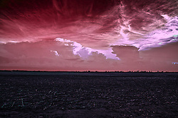 Storm clouds roll over the prairie and the uncultivated fields in the mid spring of Central Illinois.  This image was processed as a false color infrared image.