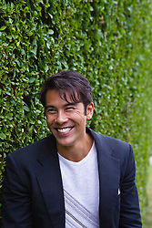 Asian American Man next to a hedge in Southampton, NY