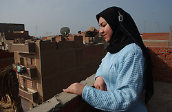 Cairo, Egpyt: Fayoume, Egypt: Oum Hashem Rashad's daughter Samah, 20,  looks from her rooftop garden in Fayoume, Egypt December 5, 2005. She is a recipient of the telefood project by FAO which has enabled her to have a small garden on her roof. The extra food has  provided an extra income for her family and also fresh, pesticide free vegetables. (Ami Vitale)