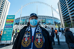 © Licensed to London News Pictures. 25/04/2021. LONDON, UK.  A Spurs fan outside Wembley Stadium for the Carabao Cup final between Manchester City and Tottenham Hotspur.   8,000 spectators, comprising fans from both teams, NHS workers and local residents will watch the match which is an official test event for the UK Government's Events Research Programme.  Data will be collected for managing and mitigating Covid-19 transmission so that venues can prepare to accommodate fuller crowds and audiences as lockdown restrictions are eased.  Photo credit: Stephen Chung/LNP