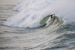 © Licensed to London News Pictures. 18/11/2018. A surfer braves Newquay's famous Cribbar waves off Towan Headland, created by wind conditions, the swell and the tide all combining. The waves, which can be over 30ft tall, are popular with experienced big wave surfers from across the world. Photo credit: Mark Hemsworth/LNP