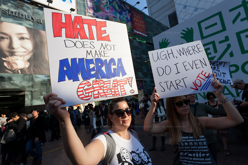 """A woman holds a sign that reads, Hate does not make America Great"""" at the Vote Out the Scandal rally at Hachiko Square, Shibuya, Tokyo, Japan. Sunday November 5th 2017. Timed to coincide with President Trumps visit to Japan, About 120 Americans living in Japan and some local Japanese  protested together from 2pm to 4pm to encourage US citizens to register to vote in future elections and call on the US government to honour it responsibilities to the American people,."""