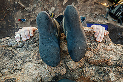Feet of climber hanging from boulder at Hueco Tanks State Park & Historic Site, El Paso, Texas. USA.