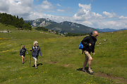 Walkers walk in Velika Planina, on 26th June 2018, in Velika Planina, near Kamnik, Slovenia. Velika Planina is a mountain plateau in the Kamnik–Savinja Alps - a 5.8 square kilometres area 1,500 metres 4,900 feet above sea level. Otherwise known as The Big Pasture Plateau, Velika Planina is a winter skiing destination and hiking route in summer. The herders huts became popular in the early 1930s as holiday cabins known as bajtarstvo but these were were destroyed by the Germans during WW2 and rebuilt right afterwards by Vlasto Kopac in the summer of 1945.