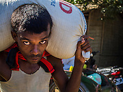 09 NOVEMBER 2014 - SITTWE, RAKHINE, MYANMAR: A Rohingya laborer carries a 50 kilo (102 pounds) sack of rice to a ration distribution in a Rohingya Muslim IDP camp near Sittwe. After sectarian violence devastated Rohingya communities and left hundreds of Rohingya dead in 2012, the government of Myanmar forced more than 140,000 Rohingya Muslims who used to live in and around Sittwe, Myanmar, into squalid Internal Displaced Persons camps. The camps are about 20 minutes from Sittwe but the Rohingya who live in the camps are not allowed to leave without government permission. The government says the Rohingya are not Burmese citizens, that they are illegal immigrants from Bangladesh. The Bangladesh government says the Rohingya are Burmese and the Rohingya insist that they have lived in Burma for generations. They are not allowed to work outside the camps, they are not allowed to go to Sittwe to use the hospital, go to school or do business. The camps have no electricity. Water is delivered through community wells. There are small schools funded by NOGs in the camps and a few private clinics but medical care is costly and not reliable.  PHOTO BY JACK KURTZ