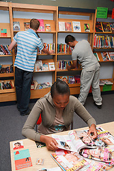 Students in library looking at books and magazines.