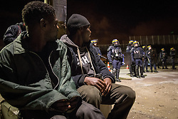 """Zwei Fluechtlinge sitzen am Rande des Camps und beobachten die Zusammenstoeflen zwischen einigen Camp-Bewohnern und der Polizei. Das sogenannte îJungleî Fluechtlingscamp am Rande der franzoesischen Stadt Calais, am Wochenende vor der angesetzten Raeumung. Viele tausend Migranten und Fluechtlinge harren teilweise seit Jahren in der Hafenstadt aus in der Hoffnung den Aermelkanal nach Groflbritannien ueberqueren zu koennen. Die franzoesischen Behoerden kuendigten an, dass sie das Camp, indem derzeit bis zu bis zu 10.000 Menschen leben K¸rze raeumen werden. / 221016<br />  <br /> ***Two refugees sitting near the camp and watching the clashes between some camp residents and police forces. So called îJungle"""" refugee camp on the outskirts of the French city of Calais on the weekend before the scheduled eviction. Many thousands of migrants and refugees are waiting in some cases for years in the port city in the hope of being able to cross the English Channel to Britain. French authorities announced that they will shortly evict the camp where currently up to up to 10,000 people live.***"""